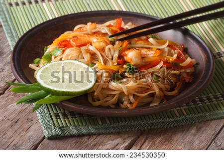 Asian food: rice noodles with shrimp and vegetables close-up on a plate. horizontal  - stock photo