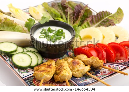 Asian food with chicken skewers, sauce, tomatoes, cucumber, pineapples, endives and salad. - stock photo