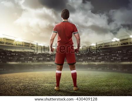 Asian football player standing on green grass stadium - stock photo
