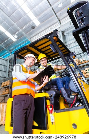 Asian fork lift truck driver discussing checklist with foreman in warehouse  - stock photo