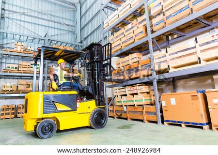 Asian fork lift truck driver lifting pallet in storage warehouse - stock photo