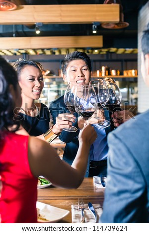 Asian friends celebrating with red wine - stock photo