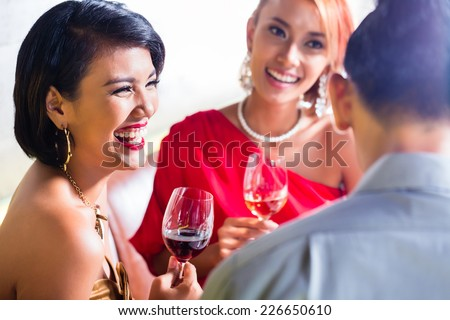 Asian friends drinking wine in fancy bar