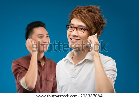 Asian friends talking to each other on the phone - stock photo