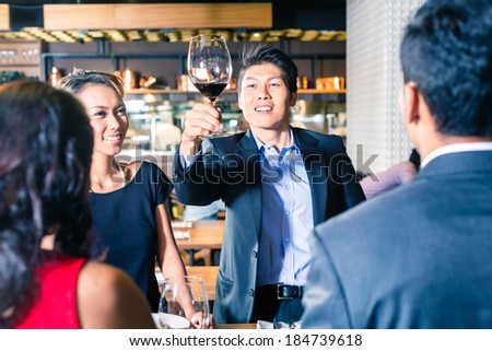 Asian friends toasting with wine - stock photo