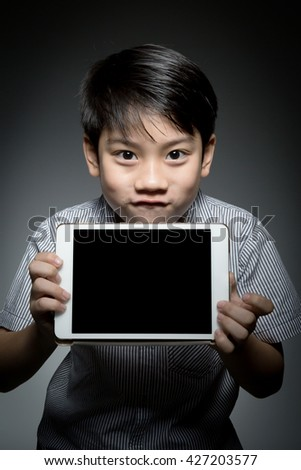 Asian funny boy with tablet computer in hand on dark gray background