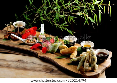 Asian Fusion appetizer plate, with Tempura, Shrimps, Spring rolls and spicy chicken - stock photo