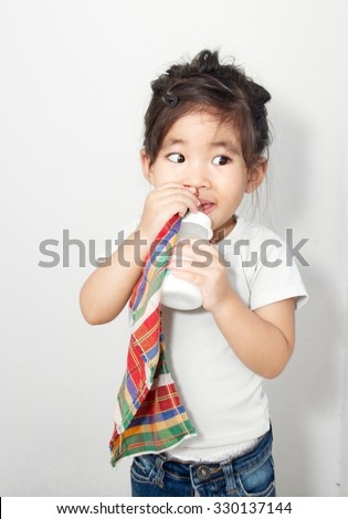 asian girl addict her textile and milk bottle - stock photo