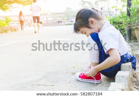 Asian girl are tying her shoes in the public park.
