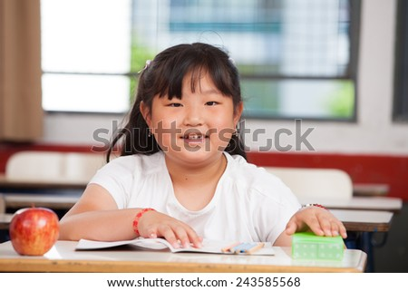 Asian girl at primary school classroom desk