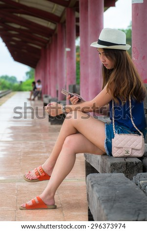 Asian girl at the railway station waiting for a train - stock photo