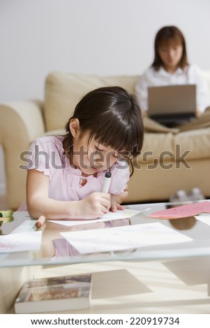 Asian girl coloring with mother in background - stock photo