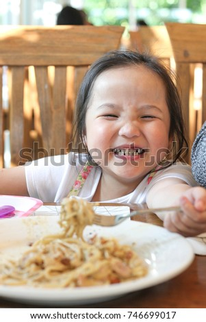 Asian girl eat spaghetti and feel so happy family time and candid photo