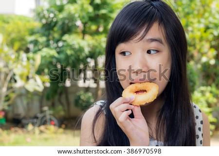 Asian girl enjoy eating fried chicken donut. - stock photo