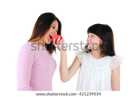 Asian girl feeding her mother with apple
