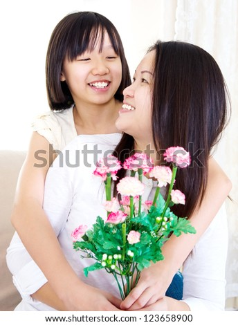 Asian girl giving carnation flower to mother on mother's day - stock photo