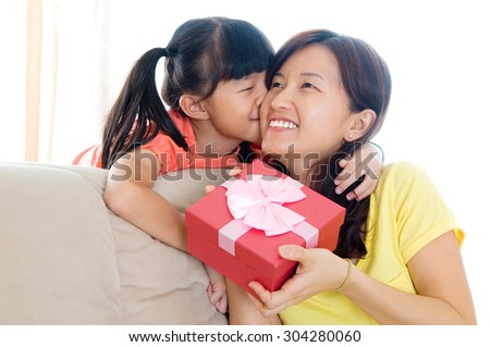 Asian girl giving present to her mother - stock photo
