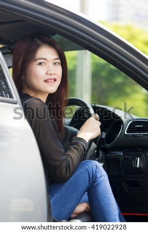 Asian Girl happy smiling in a car