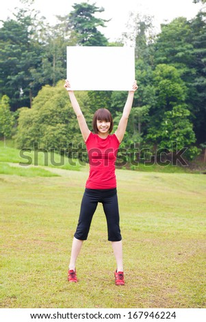 Asian girl holding a white blank card at outdoor park - stock photo