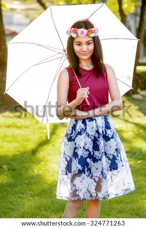 Asian girl holding an umbrella in the park