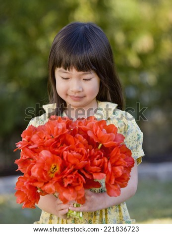 Asian girl holding bouquet of flowers