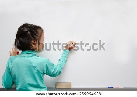 Asian girl holding pen write on white board - stock photo