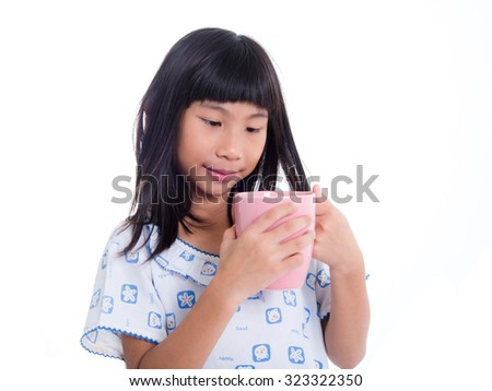 Asian girl holding pink pastel cup and smiling on white.
