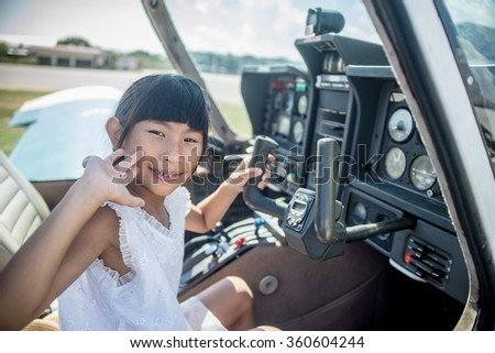 Asian girl in cockpit of plane with sunny day. - stock photo