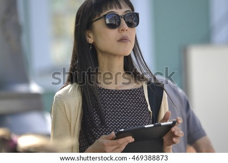 Asian girl in dark glasses holding a tablet in his hands and looks into the distance Petersburg in August 2016 in anticipation of the queue for bmletami Hermitage editorial