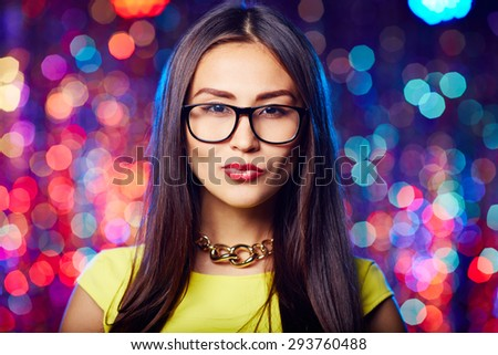 Asian girl in eyeglasses and perfect makeup looking at camera - stock photo