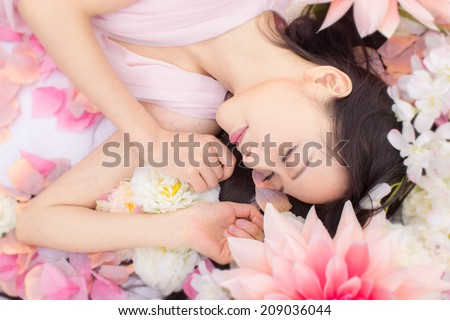 asian girl in flowers sleeping - stock photo