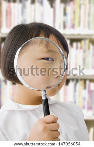 Asian girl in library holding magnifying glass