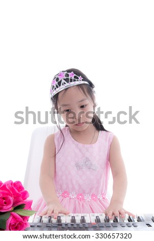 Asian girl in princess dress playing keyboard on white.