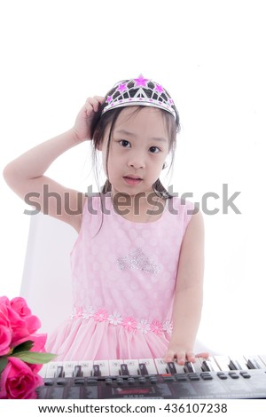 Asian girl in princess dress scratching her head during playing keyboard on white.