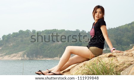 asian girl in the coastal with the sea and mountain background with innocent face and pose side view on Lamma Island in hong kong - stock photo
