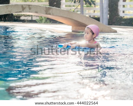 Asian girl is playing in the pool, sun set light