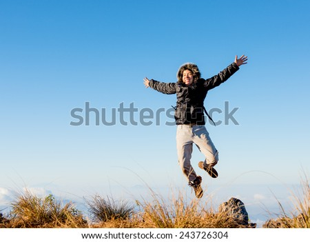 asian girl jumping on the to top of mountain, freedom and joy. - stock photo