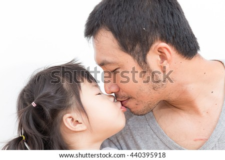 Asian girl kissing and hugging her father over white background - stock photo