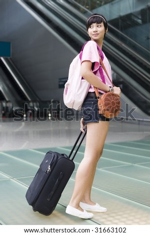 asian girl leaving singapore's changi airport terminal and turning her head back