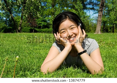 Asian girl listening to music on grass