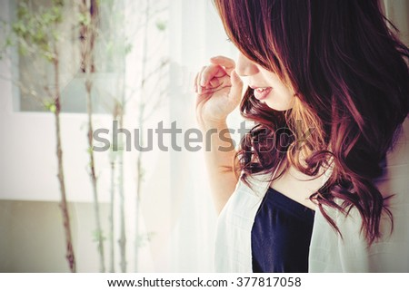Asian girl look through window in the morning with smile face, selective focus, vintage tone - stock photo