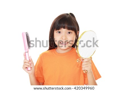 Asian girl looking at her face in mirror - stock photo