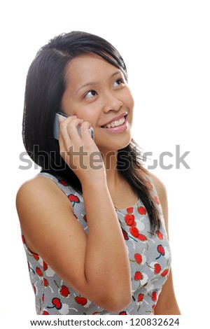 Asian girl looking happy and talking on mobile phone - stock photo