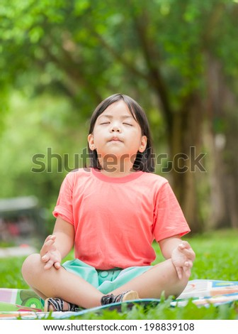 Asian girl meditates do practicing yoga on green garden park at sunny summer day - stock photo