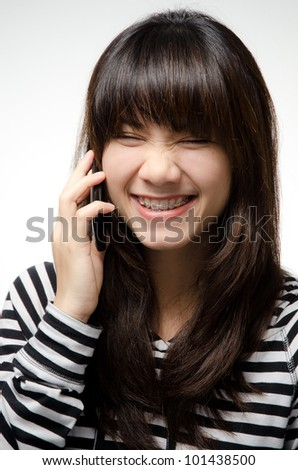 Asian girl on black and white shirt is talking on a mobile phone - stock photo