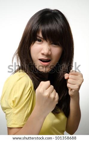 Asian girl on yellow shirt do a boxing pose - stock photo