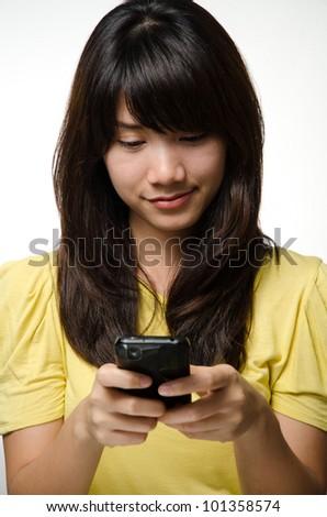 Asian girl on yellow shirt play a smart phone - stock photo