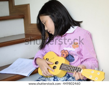 Asian girl play guitar (Ukulele)
