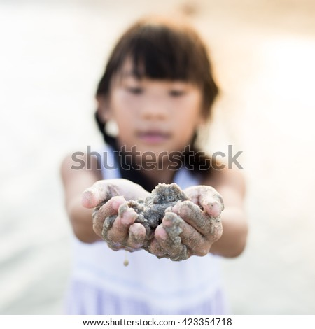 Asian girl playing on the beach with sun light.  Selective focus - stock photo