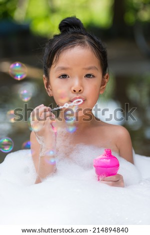asian girl playing with water and foam - stock photo
